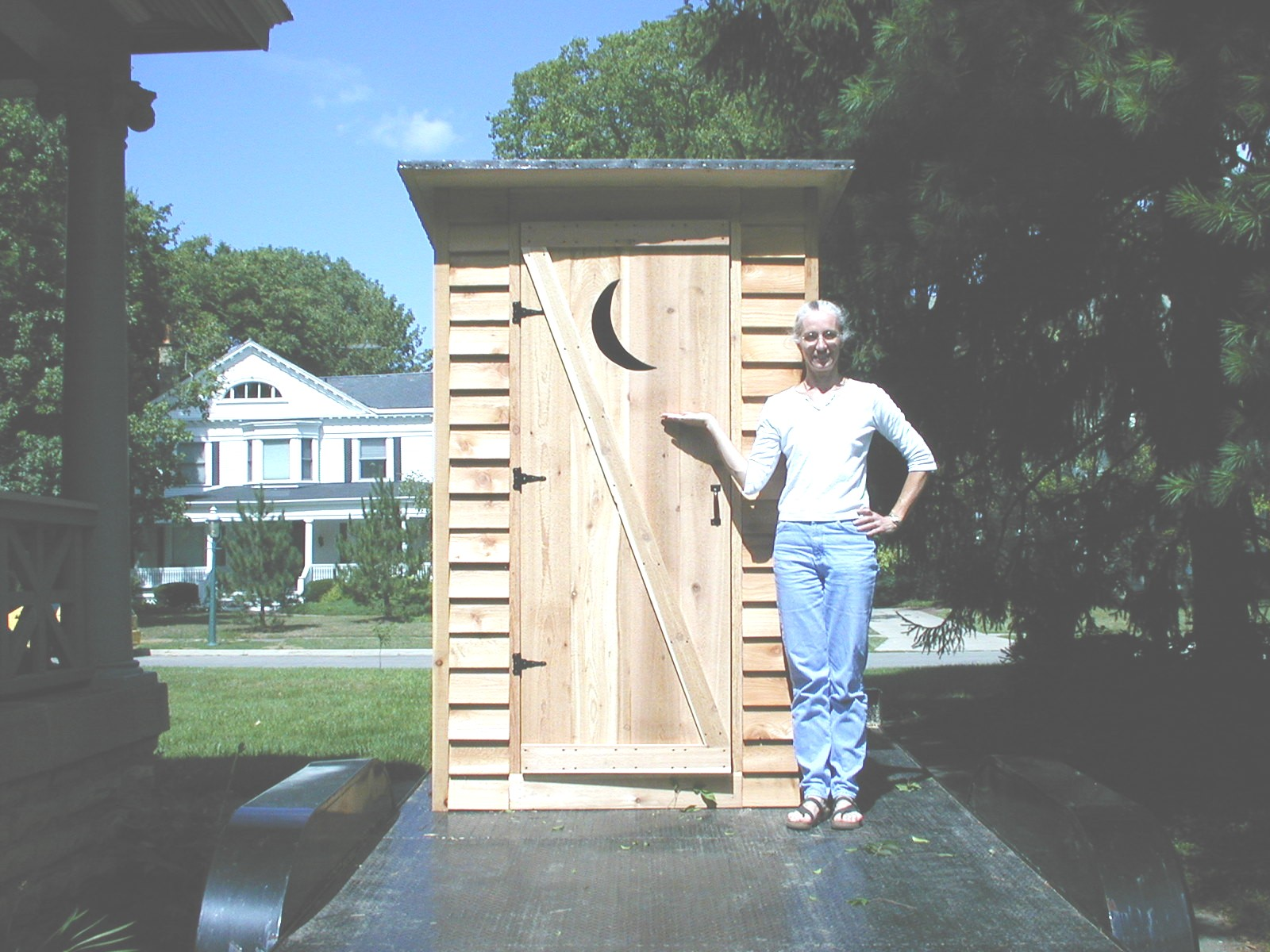 Christine proudly displays the outhouse. Note the crescent moon on the door. & outhouse Pezcame.Com